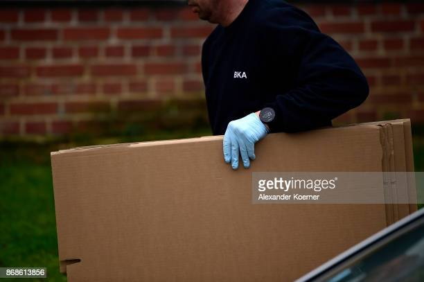 A police officer of the German Federal Police carries boxes into the apartment police raided hours before and where they arrested a Syrian man on...