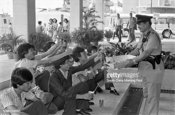 A police officer offers cakes to a group of blind and deaf youngsters outside the City Hall after their visit to a US Seventh Fleet flagship 22SEP77