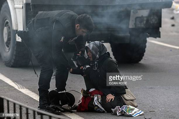 A police officer offers his gas mask to a woman crying in the street in Istanbul after Turkish antiriot police officers used tear gas to disperse...