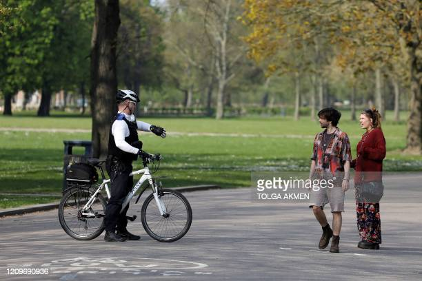 Police officer on a bicycle, tells a couple that the park is closed, and they need to leave, in Victoria Park, east London on April 11 as life in...