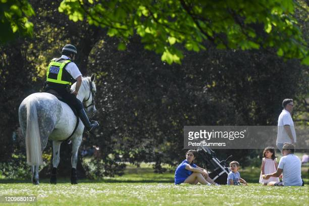 Police officer on a horse speaks to a family having a picnic in Greenwich Park on April 11, 2020 in London, England. Public Easter events have been...