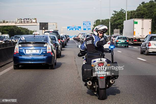 A police officer on a motorbike directs traffic as French cab drivers block roads during a protest against Uber Technologies Inc's car sharing...