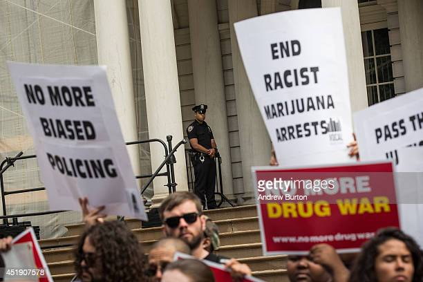 Police officer on the steps of New York City Hall monitors a protest in support of the proposed Fairness and Equity Act, which would attempt to...