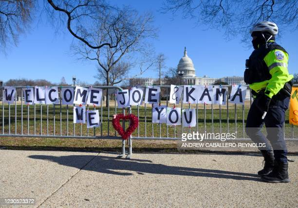 Police officer passes signs of support for President-elect Joe Biden and Vice President-elect Kamala Harris near the US Capital in Washington, DC on...