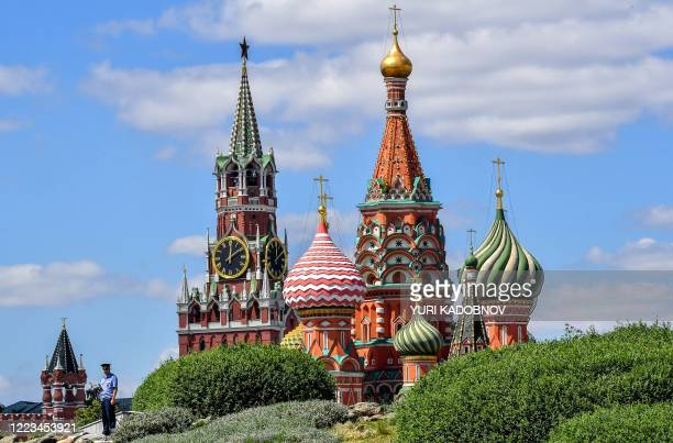 Police officer patrols at the Zaryadye park with the Kremlin's Spasskaya tower and St. Basil's Cathedral on the background in central Moscow on June...