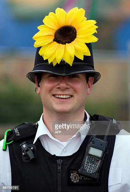 A police officer patrols the site while wearing a plastic sunflower on the final evening of the annual Glastonbury festival near Glastonbury Somerset...