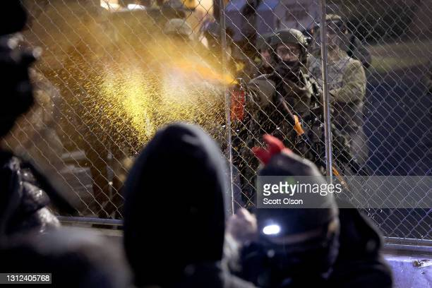 Police officer pepper sprays demonstrators protesting the shooting death of Daunte Wright face off with police near the Brooklyn Center police...