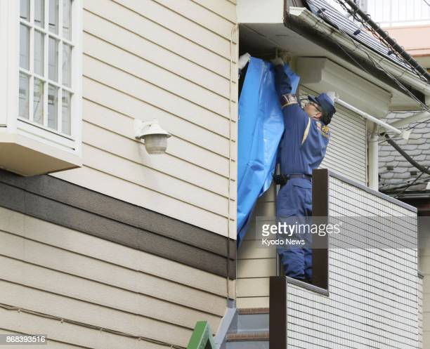 A police officer places a blue sheet on part of an apartment house in Zama Kanagawa Prefecture on Oct 31 2017 where police found nine dismembered...