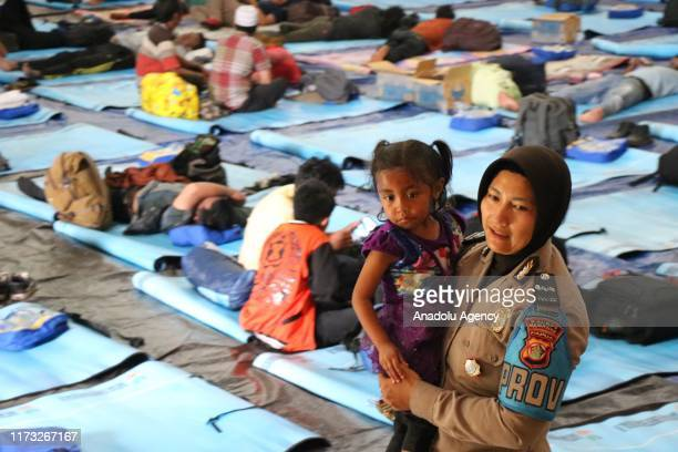 Police officer played with refugee children fled from various region in Papua at a Sport Center on October 3, 2019 in Merauke, Papua, Indonesia. At...