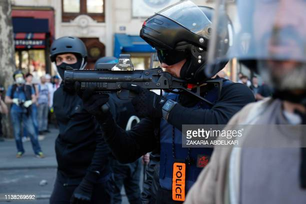 Police officer points a 40-millimetre rubber defensive bullet launcher LBD during clashes at the Place de la Republique during an anti-government...