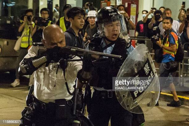 TOPSHOT A police officer points a firearm during a clash with protesters who had gathered outside Kwai Chung police station in support of protesters...