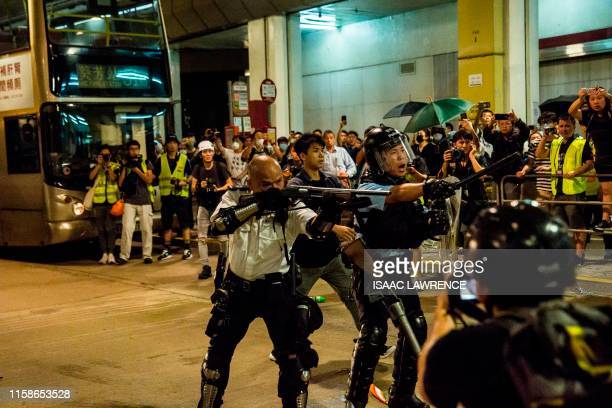 A police officer points a firearm during clashes with protesters who had gathered outside Kwai Chung police station in support of protesters detained...