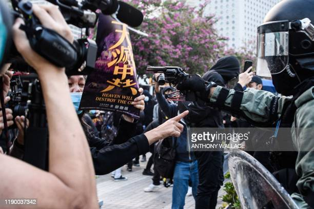 TOPSHOT A police officer points a pistol during a rally in Hong Kong on December 22 2019 to show support for the Uighur minority in China Hong Kong...