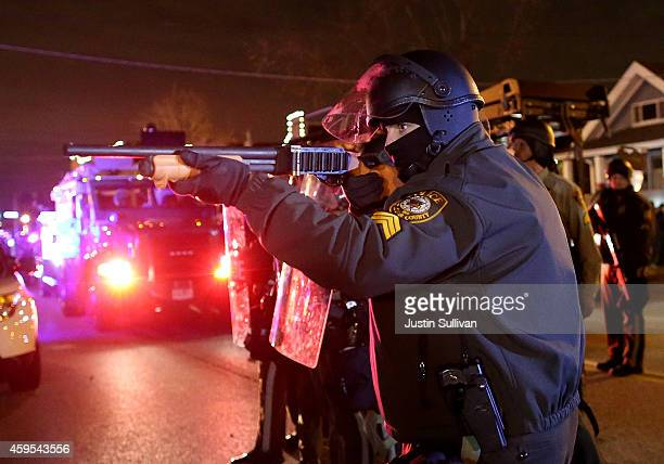 A police officer points a shotgun at protestors during a demonstration on November 24 2014 in Ferguson Missouri A St Louis County grand jury has...