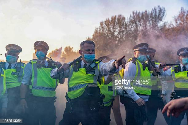 Police officer points at protesters as they clash after demonstrations at Hyde Park. People called online to a flash mob-style mass gathering against...