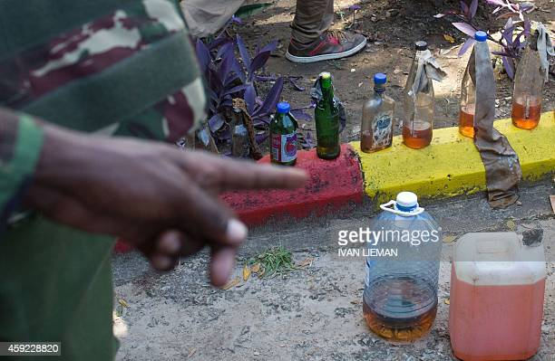 A police officer points to jars containing various chemicals including petrol seized following a raid on the Masjid Swafaa mosque during a security...