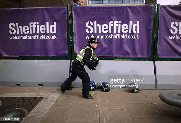 Police officer prepares riot helmets as demonstrators gather outside Sheffield City Hall, where the Liberal Democrats' spring conference is taking...