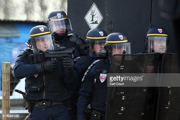 Police officer prepares to fire tear gas during clashes as part of the 'jungle' migrant camp is cleared on February 29, 2016 in Calais, France The...