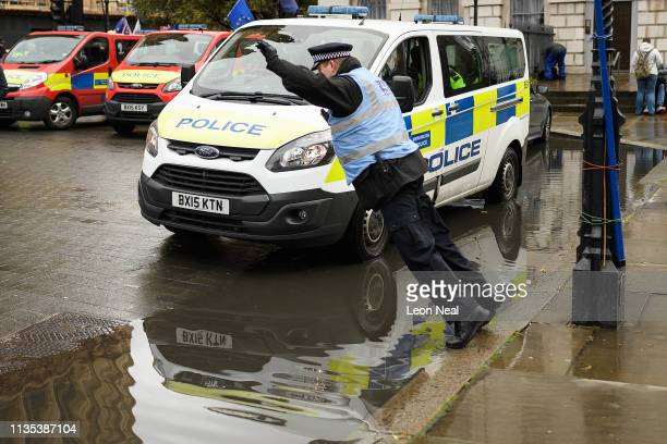 Police officer prepares to leap across a puddle as people take part in Brexit demonstrations outside the Houses of Parliament on March 12, 2019 in...