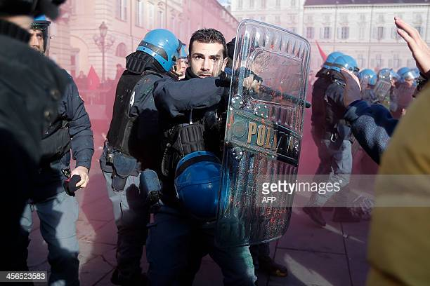 Police officer protects himself with his shield as police clash with students during a protest against the local government in downtown Turin on...