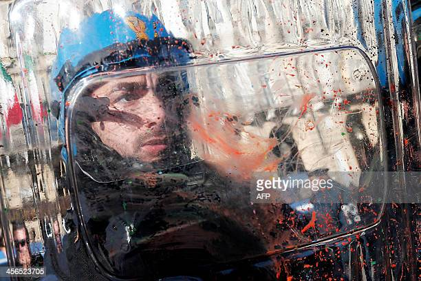 Police officer protects himself with his shield as protesters throw paint bombs during a protest by students against the local government in downtown...