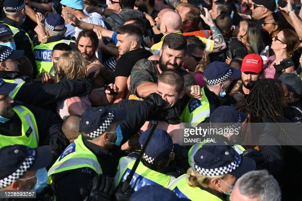 TOPSHOT A police officer punches a demonstrator at an antivax rally protest against vaccination and government restrictions designed to control or...