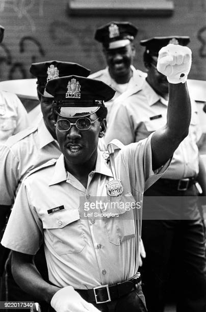 Police officer raises a closed fist 'black power' salute during, West Philadelphia, Pennsylvania, 1968. He was attending a demonstration march of the...