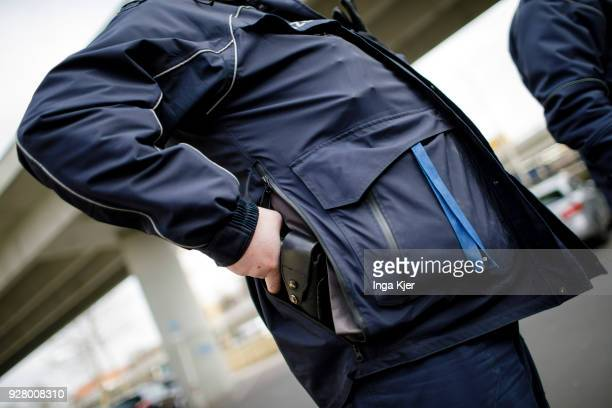 A police officer reaches for his service weapon on February 27 2018 in Berlin Germany