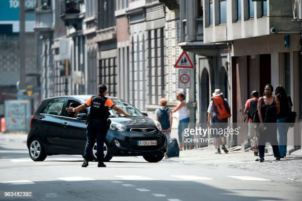 A police officer redirects a car in the eastern Belgian city of Liege on May 29 after an armed man shot and killed two police officers before being...