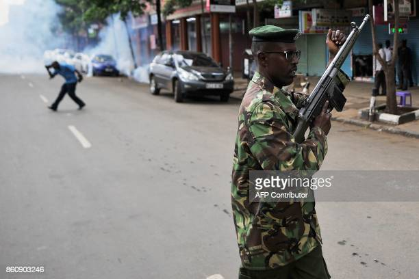 TOPSHOT A police officer reloads his rifle as he prepares to fire in the air to attempt to disperse groups of demonstrators on October 13 in Nairobi...