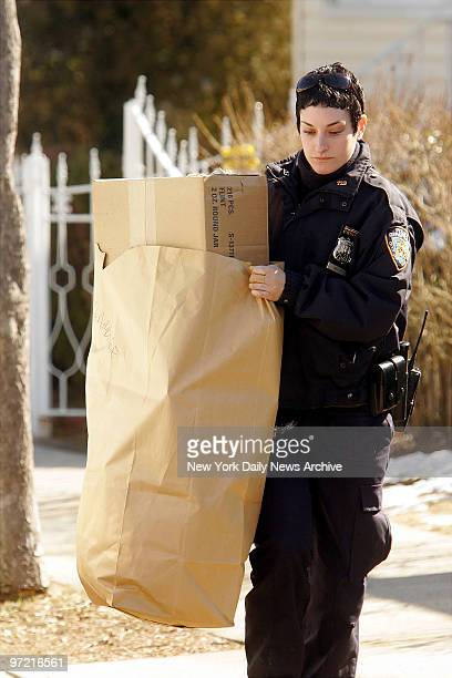 A police officer removes a bag of evidence from the home of Darryl Littlejohn in Jamaica Queens Littlejohn a bouncer at the bar where Imette St...