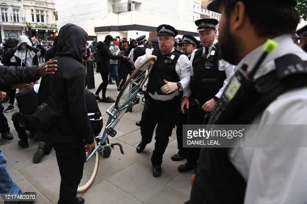 Police Officer removes a bike that was thrown by protestors, during an anti-racism demonstration in London, on June 3 after George Floyd, an unarmed...