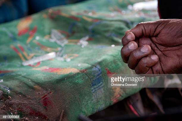 A police officer removes a piece of glass from the back seat of a vehicle after two improvised explosive devices went off in Gikomba market on May 16...