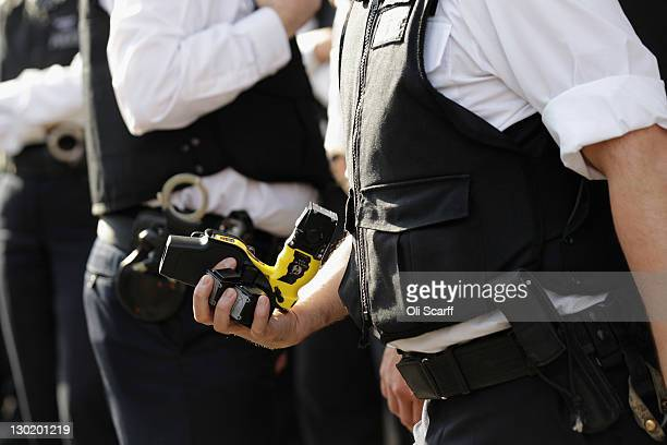 A police officer removes a TASER weapon from a colleague as protesters from 'UK Uncut ' demonstrate outside Her Majesty's Revenue and Customs on...