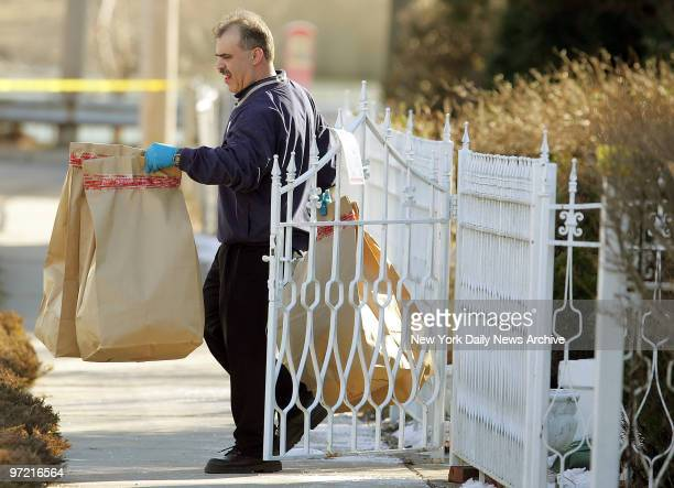 A police officer removes bags of evidence from the home of Darryl Littlejohn in Jamaica Queens Littlejohn a bouncer at the bar where Imette St...