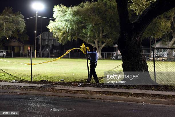 A police officer removes crime scene tape after a shooting at a playground on November 22 2015 in New Orleans Louisiana According to reports as many...