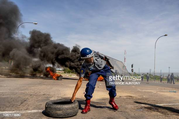 A police officer removes tyres set by protesters during a stayaway demonstration against the doubling of fuel prices on January 14 2019 in...