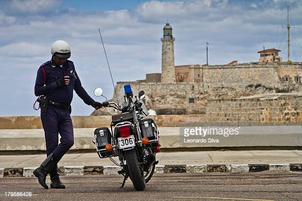 Police officer resting on his motorcycle while checking a device at a checkpoint near the ocean.