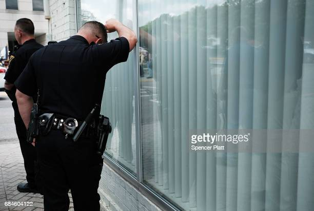 A police officer rests his head on a window during a ceremony honoring area soldiers on May 18 2017 in Morgantown West Virginia West Virginia a state...