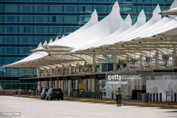 A police officer rides his bike along an empty passenger drop off area at Denver International Airport as the coronavirus pandemic slows air travel...