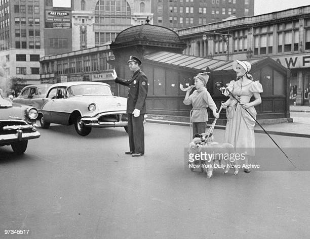 Police Officer Ruben Kasten holds up traffic to permit Little Boy Blue and Little Bo Peep and their lambs to cross to the Coliseum at 59th St and...