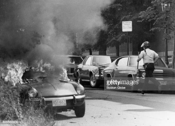 A police officer runs down Washington Street as a car burns due to demonstrations against the desegregation of public schools in the Charlestown...