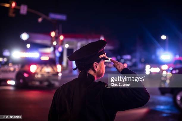 Police officer salutes as a procession carrying the body of a fellow officer leaves King Sooper's grocery store where a gunman opened fire on March...