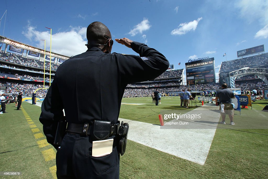 A police officer salutes during the playing of the national anthem before the game between the Jacksonville Jaguars and the San Diego Chargers at Qualcomm Stadium on September 28, 2014 in San Diego, California.