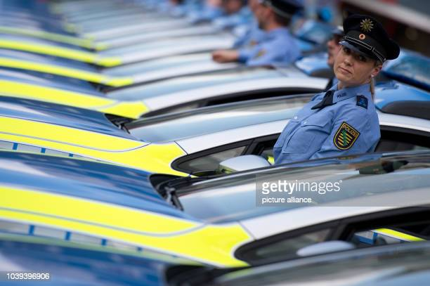 Police officer Sandra Cebulla stands next to a vehichle during the handover of 34 new interactive patrol cars on Hauptmarkt square in Zwickau,...