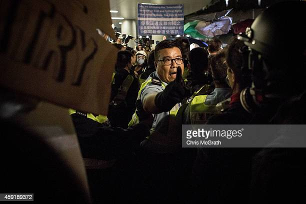 Police officer screams at pro-democracy activists as clashes broke out in front of the Legislative Council building on November 19, 2014 in Hong...