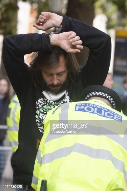 A police officer searches a protester from the environmentalist group 'Extinction Rebellion' in London United Kingdom on October 9 2019 The...