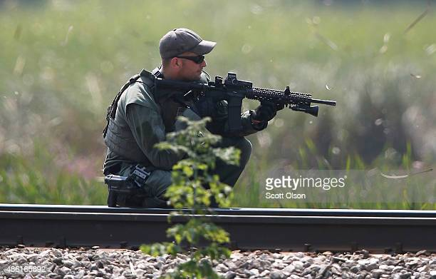 Police officer searches an area for suspects involved in shooting an officer September 1, 2015 in Fox Lake, Illinois. A manhunt for three suspects is...