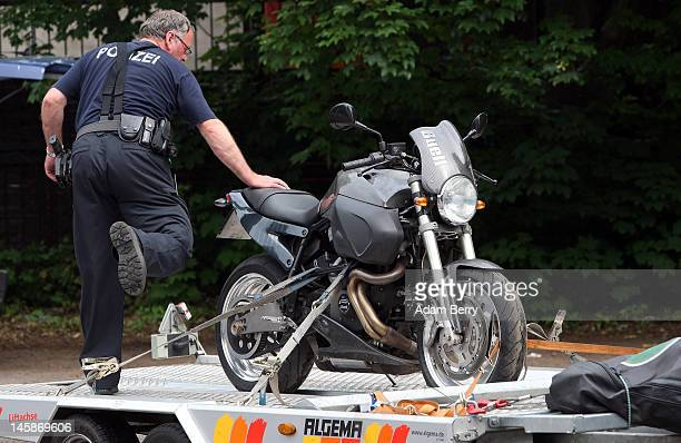 A police officer secures a motorcycle that has been seized at the clubhouse of the motorcycle gang Bandidos Del Este to the back of a police van on...