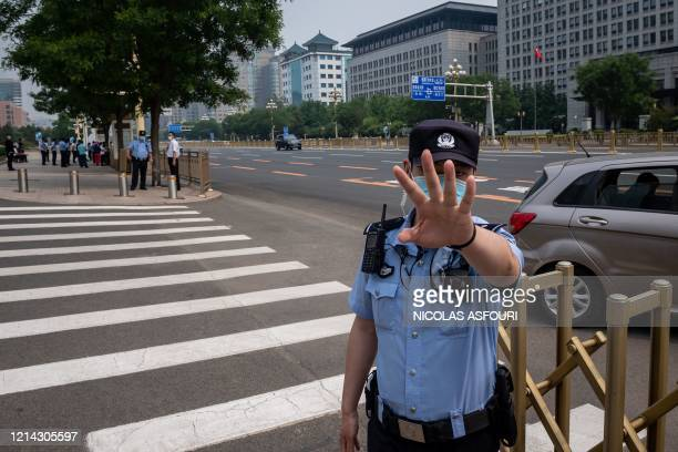 Police officer secures an area and gestures before a convoy of buses transporting delegates passes by ahead of the opening ceremony of the Chinese...